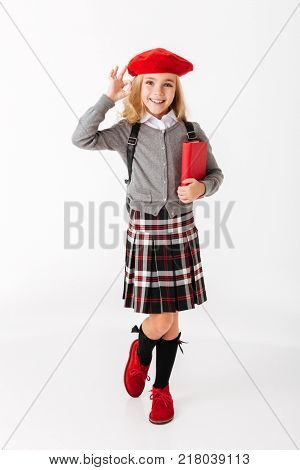 Full length portrait of a cute little schoolgirl dressed in uniform with backpack holding book and showing ok gesture isolated over white background