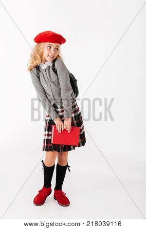 Full length portrait of a cute little schoolgirl dressed in uniform with backpack holding book and looking away at copy space isolated over white background