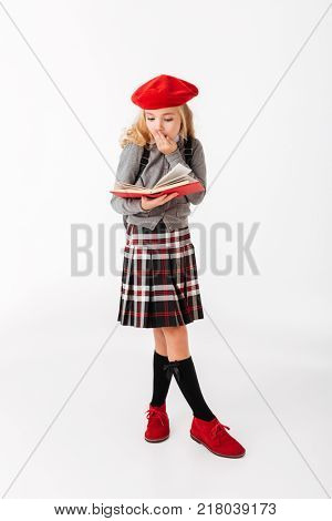Full length portrait of a shocked little schoolgirl dressed in uniform with backpack reading book while standing isolated over white background