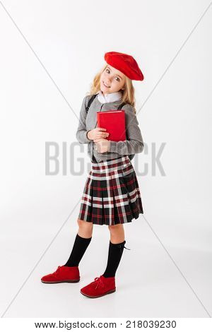 Full length portrait of a lovely little schoolgirl dressed in uniform with backpack holding book and looking at camera isolated over white background