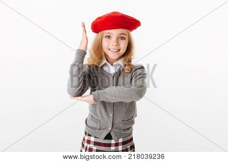 Portrait of a smiling little schoolgirl dressed in uniform standing and holding hand for an answer isolated over white background
