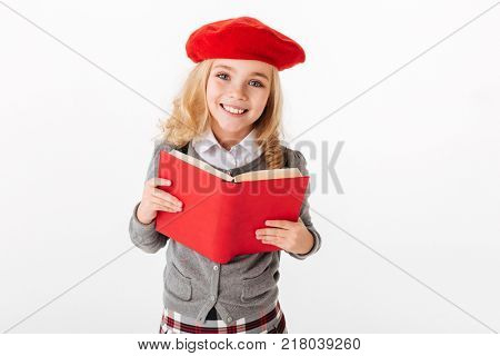 Close up portrait of a smiling little schoolgirl dressed in uniform holding book and looking at camera isolated over white background