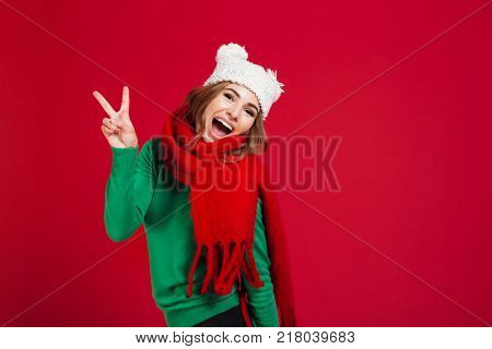 Joyful screaming brunette woman in sweater, funny hat and scarf showing ok sign and looking at the camera over red background