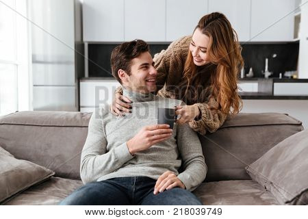 Image of young happy young woman gives a cup with hot tea or coffee to her man.
