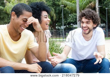 Laughing caucasian man talking with african american and latin friends outdoor in the summer