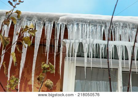 White Snow On The Roof Of A Red Brick House And Icicles Hanging From A Slate Roof