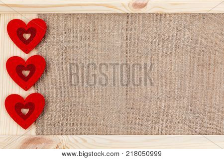 Heart on a wooden background covered with burlap a card for Valentine's Day. With some free space for your text or sign. Valentines day