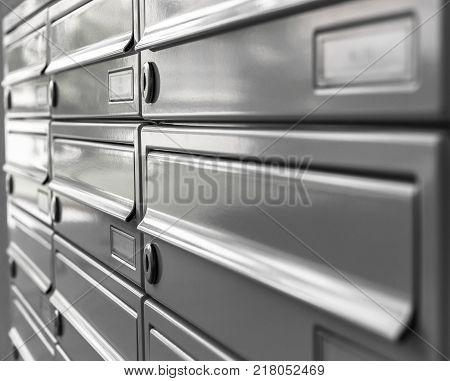 Grey new postbox in condominium. Defocused blurry background.