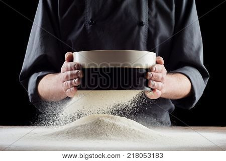 Male hands sifting flour from old sieve on old wooden kitchen table. Isolated on black background