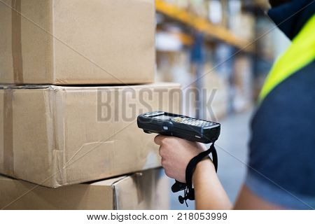 Unrecognizable male warehouse worker with barcode scanner.
