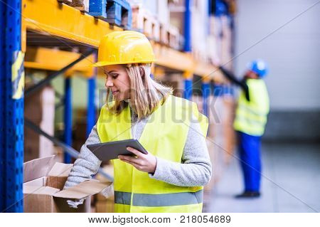 Young woman worker or supervisor with tablet. Warehouse workers controlling stock.