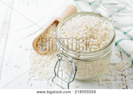 Raw White rice variety Arborio for Italian risotto dishes in glass jar on dark wooden background. Selective focus. Copy space.