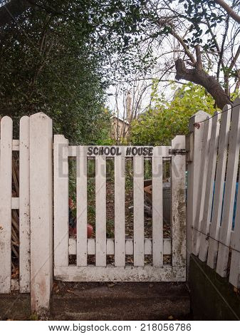 Black Lettering School House White Picket Gate Fence Country House Close Up