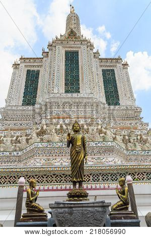 Buddha statue and statues of disciples at Wat Arun against a clouds and blue sky.