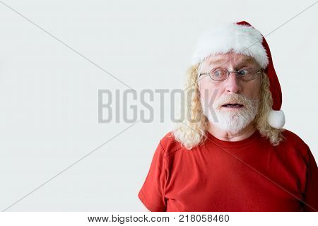 Portrait of Santa Claus trying to remember something. Elderly man in Santa hat thinking about something. Studio shot of old man dressed for Christmas