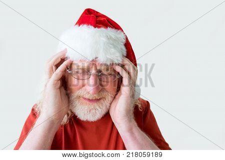 Santa Claus having headache. Portrait of old man suffering from severe migraine. Elderly man in Santa hat