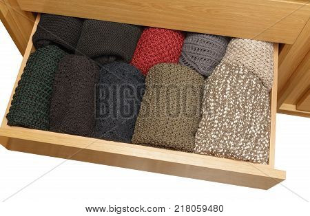 A well-organized open closet drawer. neatly stacked in piles. Storage system. Wardrobe order over white background