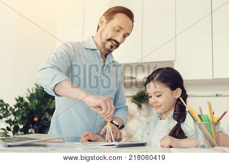 Geometry lesson. Joyful nice intelligent man standing at the table and using a pair of compasses while having a geometry lesson with his daughter