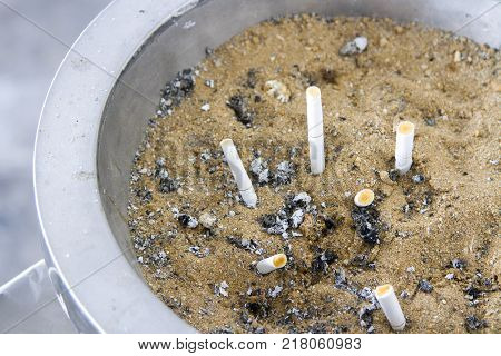 Sandbox ashtray in silver container and cigarette stub