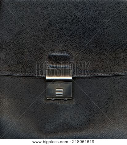 Black leather background textured with graining patterns and lock