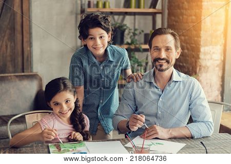 Talent and creativity. Cheerful positive happy family sitting at the table and looking at you while painting together