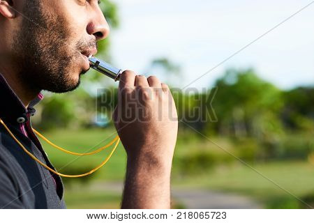 Close-up shot of bearded soccer referee blowing whistle after noticed infringement of game rules, blurred background