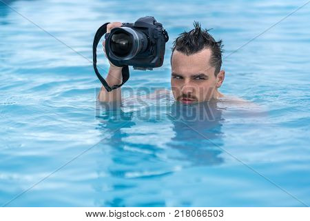 Funny guy holds a black camera in the geothermal pool outdoors in Iceland. He looks to the side with a grimace on the face. Closeup. Horizontal.
