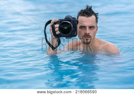 Ridiculous guy holds a black camera in the geothermal pool outdoors in Iceland. He looks to the side with a grimace on the face. Closeup. Horizontal.