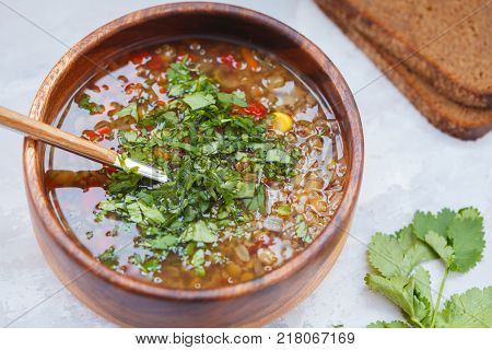 Peruvian soup with quinoa red rice and lentils in a wooden bowl with herbs and rye bread. Healthy vegan food concept.