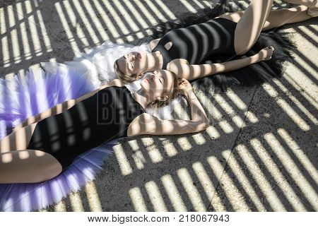 Cute ballerinas with closed eyes lying on the multicolored tutus on the concrete floor outdoors. They wear black leotards. Sunlight creates stripe shadows on them. Horizontal.