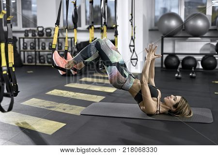 Athletic girl is training with TRX straps in the gym. She leans on her shoulders on the mat while her feet are in the straps in the air. Woman wears colorful pants with black top and pink sneakers.