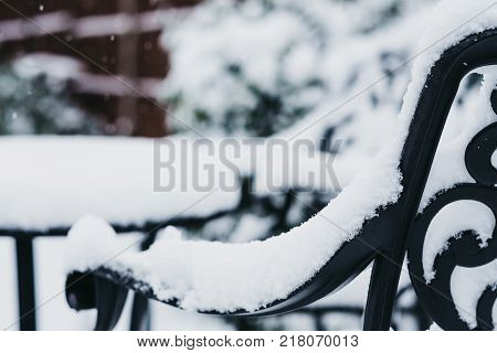 Close up of a black metal garden furniture in a garden in winter, covered in snow, snowing, selective focus.