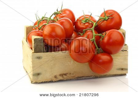 fresh tomatoes on the vine in a wooden crate