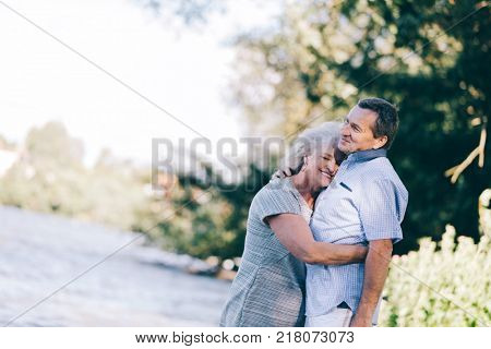Senior woman hugging her husband lovingly. Romantic date in the bosom of nature.