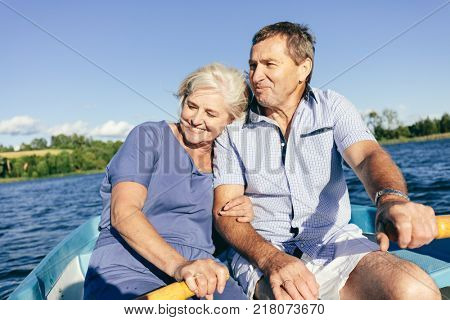 Older couple cuddling on a boat. Happy romantic relationship. Summer activities.