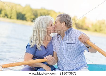 Elderly couple kissing, sailing on a boat together. Life companions. Love concept.