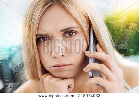 Boring waiting. Beautiful funny young woman waiting for interlocutor and holding the phone while looking straight