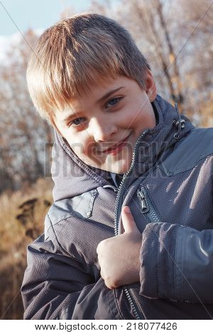 Funny Blond Boy In Yellow Grass In An Autumn Day
