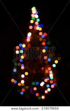 christmas fir with defocused colored lightings at night