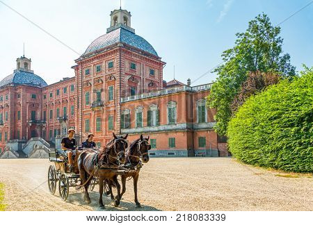 Racconigi Italy - June 28 2015: A carriage with toung people in the Royal Castle garden