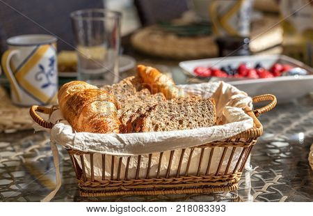 Sliced black integral bread and croissant in a basket. Close-up.
