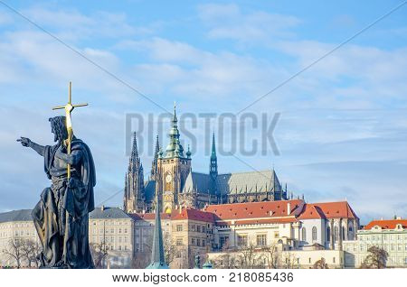 Religous statue on Charles Bridge with St Vitus Cathedral in background