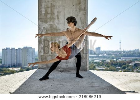 Amazing couple of ballet dancers posing on the concrete floor of the unfinished building on the cityscape background. Topless guy wears a black dance pants, girl wears a red-gray leotard. Horizontal.