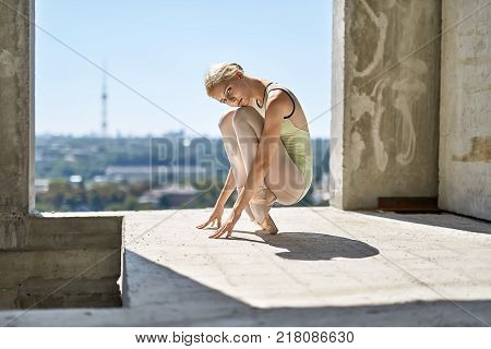 Gorgeous ballerina is posing on the concrete floor of the unfinished building on the cityscape background. She wears a green leotard with light leggings and pointe shoes. Sun shines onto her body.