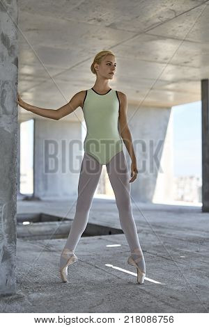 Charming ballerina is posing on the concrete floor of the unfinished building. She wears a green leotard with light leggings and pointe shoes. Girl stands on the pointes and looks to the side.