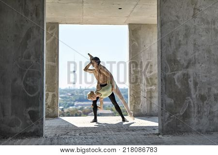 Sensual couple of ballet dancers posing on the concrete floor of the unfinished building on the cityscape background. Topless guy wears a black dance pants, girl wears a green leotard. Horizontal.