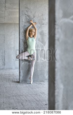 Beautiful ballerina leans on the concrete wall on the floor of the unfinished building. She wears a green leotard with light leggings and pointe shoes. She stands on left toe and looks to the side.