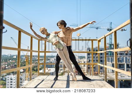 Incredible couple of ballet dancers posing on the concrete balcony of the unfinished building on the cityscape background. Topless guy wears a black dance pants, girl wears a green leotard.