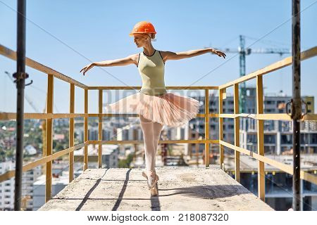 Joyful ballerina stands on the toes on the concrete balcony of the unfinished building on the cityscape background. She wears green leotard, peach tutu, leggings, pointes and construction helmet.