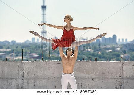 Strong dancer holds a ballerina over his head on the background of the concrete wall and cityscape. Guy wears a white dance pants. Girl wears a red skirted leotard, light leggings and pointe shoes.